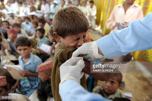 A Pakistani health worker gives a hepatitis vaccination to a flood affected boy at a makeshift school on higher ground in southern Sindh province's...