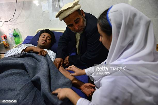 A Pakistani health worker treats an injured student at a hospital a day after an attack by Taliban militants at an armyrun school in Peshawar on...