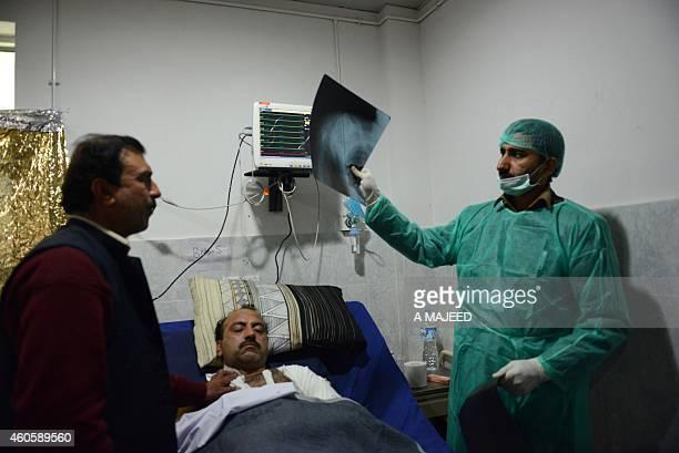 A Pakistani health worker treats injured teacher Zulfiqar at a hospital a day after an attack by Taliban militants at an armyrun school in Peshawar...