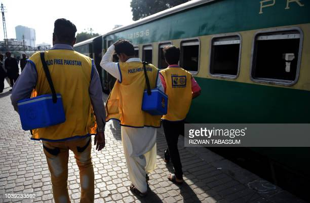 Pakistani health workers arrive at a railway station to administer polio vaccine drops to children during a polio vaccination campaign in Karachi on...