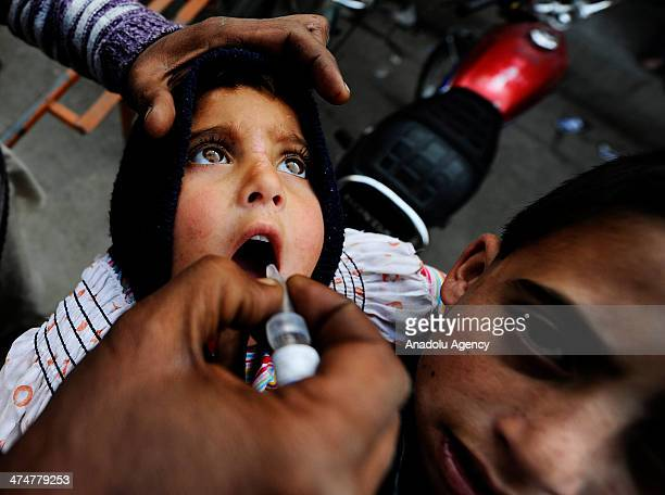 Pakistani health workers mark the thumb of a child after giving him polio vaccine drops to a child during a polio vaccination campaign in Rawalpindi...