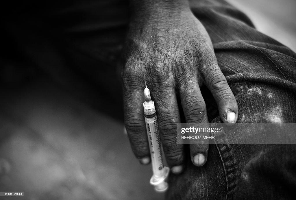 A Pakistani heroin addict, holds a syrin : News Photo