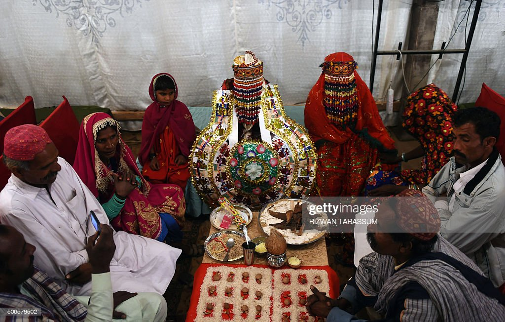 A Pakistani Hindu couple performs a Hindu ritual during a mass wedding ceremony in Karachi on January 24, 2016. Some 60 Hindu couples took part in a mass wedding ceremony organised by the Pakistan Hindu Council. / AFP / RIZWAN
