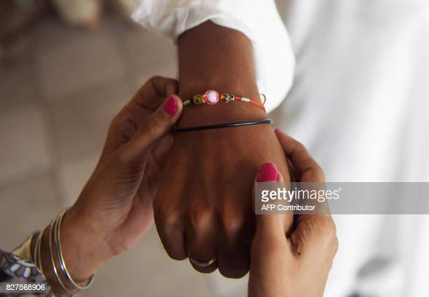 A Pakistani Hindu girl ties a sacred thread or rakhi onto her brother's wrist during the festival of Raksha Bandhan at the Lakshmi Narayan temple in...