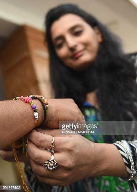 Pakistani Hindu sister ties a 'rakhi' sacred thread onto the wrist of her brother on the occasion of the Hindu festival Raksha Bandhan in Karachi on...