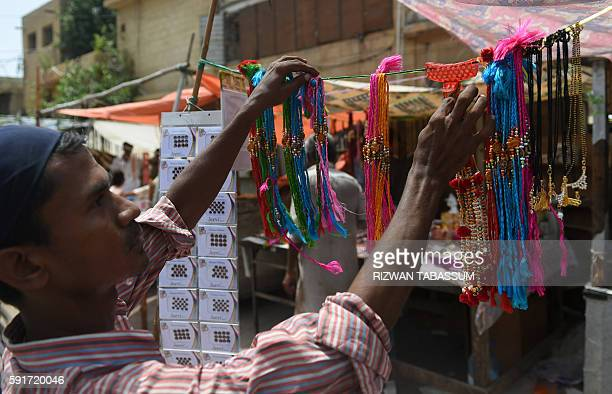 Pakistani Hindu vendor arranges rakhis or sacred thread on the occasion of the Hindu festival Raksha Bandhan at a roadside stall in Karachi on August...