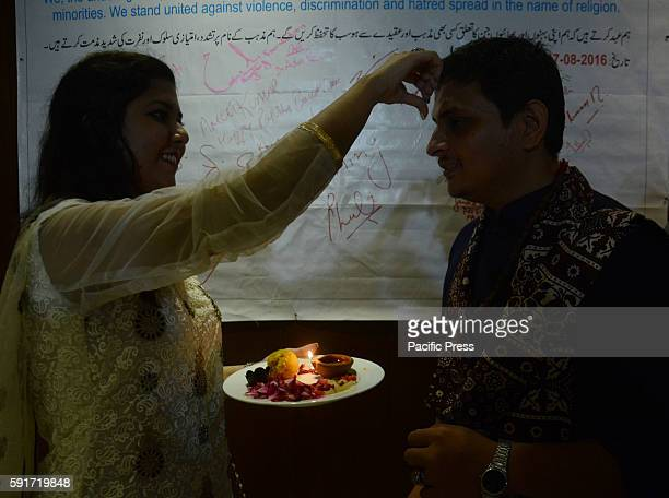 Pakistani Hindu woman performing religious rituals after tying Rakhi on the wrist of her brother on the occasion of Hindu Festival Raksha Bandhan in...