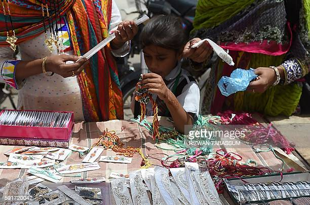 Pakistani Hindu women buy rakhi or sacred thread on the occasion of the Hindu festival Raksha Bandhan at a roadside stall in Karachi on August 18...
