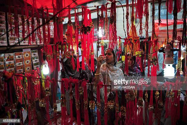 Pakistani Hindu women look at 'rakhi' at a roadside shop ahead of the Hindu festival Raksha Bandhan in Karachi on August 9 2014 The annual festival...