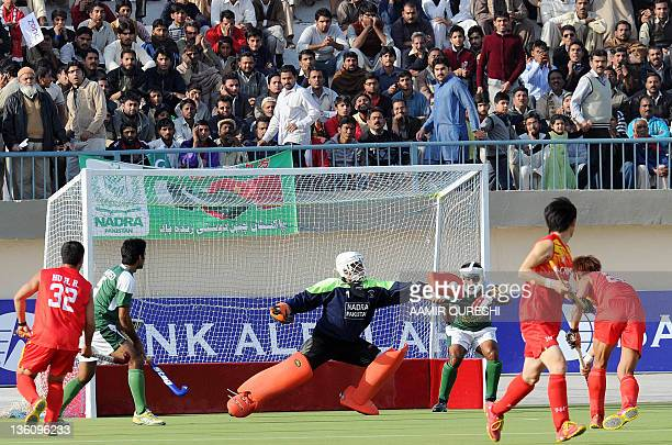 Pakistani hockey goalkeeper Imran Shah stops an attempt by China during the third field hockey match between Pakistan and China in Faisalabad on...