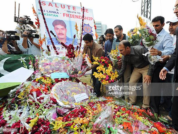 Pakistani hockey team officials and players place flowers to pay tribute to the victims at the site of the deadly ambush on the Sri Lankan cricket...