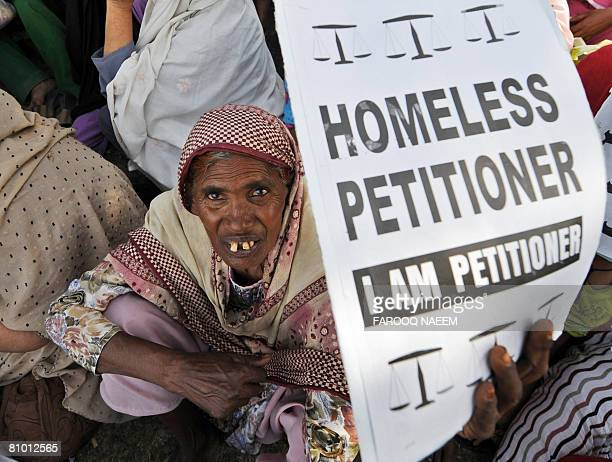 A Pakistani homeless elderly woman holds her application for an allotment of land during a protest in front of the parliament house in Islamabad on...