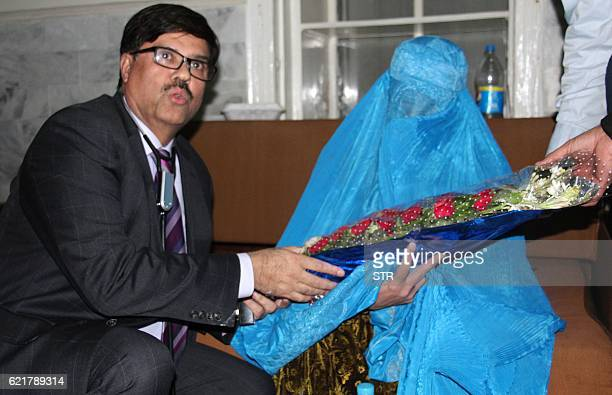 A Pakistani hospital official gives flowers to Afghan refugee woman Sharbat Gula as she leaves the Lady Reading Hospital where she was treated in...