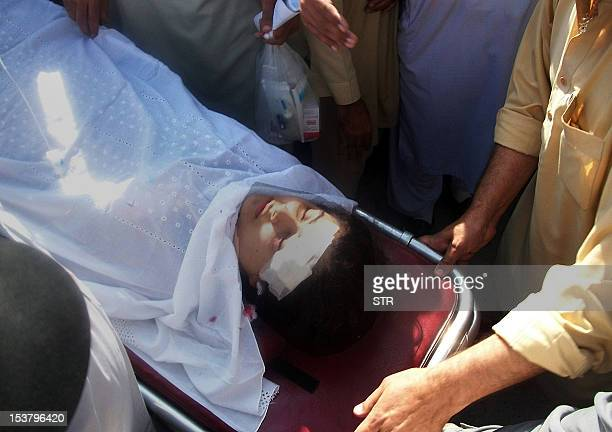 Pakistani hospital workers carry injured Malala Yousafzai on a stretcher at a hospital following an attack by gunmen in Mingora on October 9 2012 A...