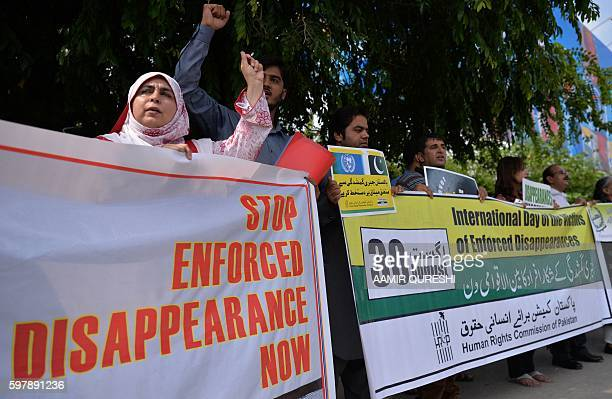 Pakistani human rights activists carry placards and banners during a protest for missing persons to mark the International Day of the Victims of...