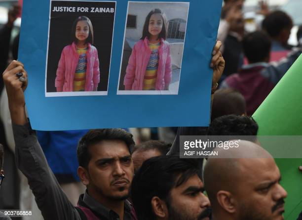 Pakistani human rights activists carry placards and banners during a protest against the rape and murder of a child in Karachi on January 11 2018 At...
