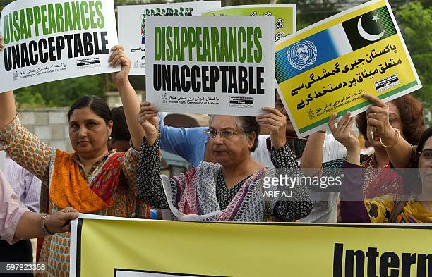 Pakistani human rights activists carry placards during a protest for missing persons to mark the International Day of the Victims of Enforced...