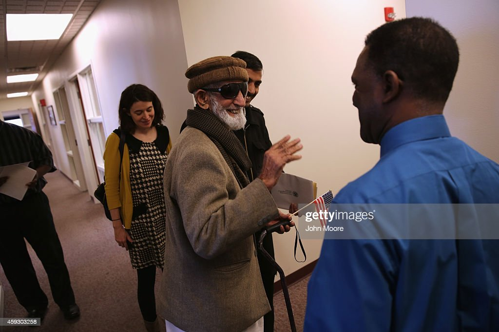 Pakistani immigrant Amanat Ali, 82, smiles after taking the oath of citizenship to the United States on November 20, 2014 in Newark, New Jersey. Supervisory immigration officer Charles Pitt, (R), administered to oath in a private natualization ceremony in the office of the U.S. Immigration and Citizenship Services (USCIS), at Newark's Federal Building.