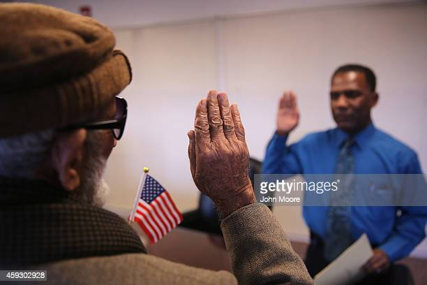 Pakistani immigrant Amanat Ali takes the oath of citizenship to the United States on November 20 2014 in Newark New Jersey Supervisory immigration...