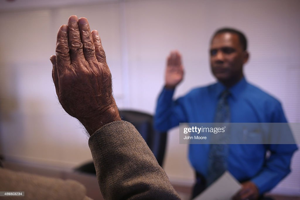 Pakistani immigrant Amanat Ali, 82, (L), takes the oath of citizenship to the United States on November 20, 2014 in Newark, New Jersey. Supervisory immigration officer Charles Pitt, (L), administered to oath in a private natualization ceremony in the office of the U.S. Immigration and Citizenship Services (USCIS), at Newark's Federal Building.
