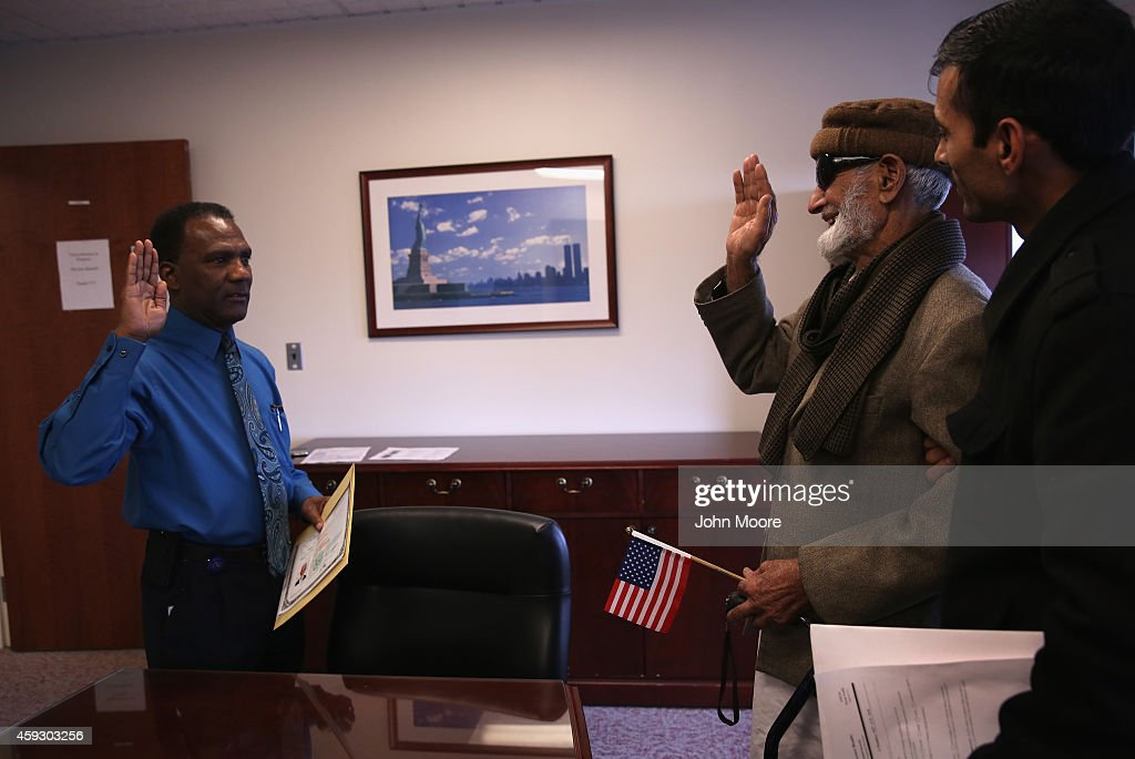Pakistani immigrant Amanat Ali, 82, takes the oath of citizenship to the United States on November 20, 2014 in Newark, New Jersey. Supervisory immigration officer Charles Pitt, (L), administered to oath in a private natualization ceremony in the office of the U.S. Immigration and Citizenship Services (USCIS), at Newark's Federal Building.