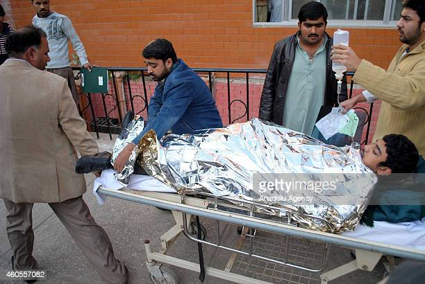 Pakistani injured student is carried to the hospital after Taliban assault on an armyrun school in the northwestern city of Peshawar Pakistan on...