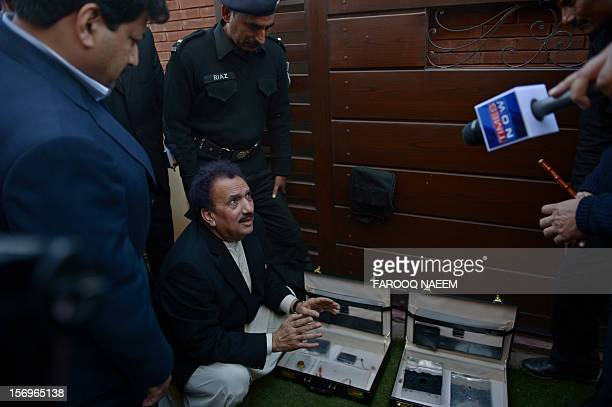 Pakistani Interior Minister Rehman Malik inspects the bomb planted device as journalist and television anchor Hamid Mir looks on in Islamabad on...