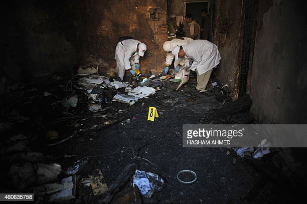 Pakistani investigative personnel collect evidence at the site of an attack by Taliban militants on an armyrun school in Peshawar on December 18 2014...