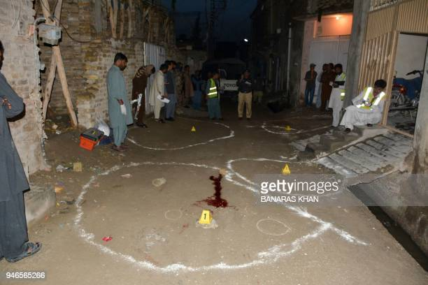 Pakistani investigators collect evidence at the shooting site outside a church in Quetta on April 15 2018 Two Christians were killed in a driveby...