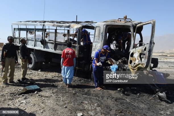 Pakistani investigators collect evidence from a burnt police truck after a suicide blast on the outskirts of Quetta on October 18 2017 At least six...