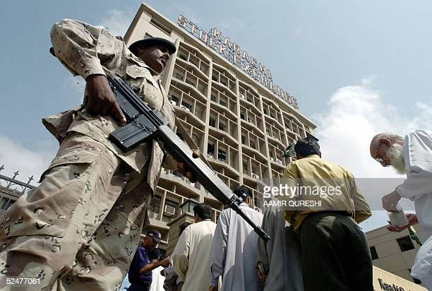 Pakistani investors stand in queue to get frisked before entering the Karachi Stock Exchange building as paramilitary soldiers stand guard in Karachi...
