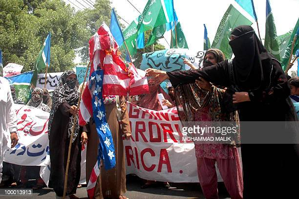 Pakistani Islamist women set a US national flag alight during a protest in Multan on May 20 against the published caricatures of Prophet Mohammed on...