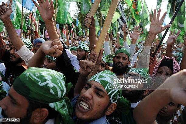 Pakistani Islamists and supporters of convicted killer Malik Mumtaz Hussain Qadri, shout slogans as they march during a protest against a court...