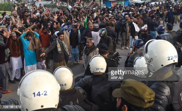 Pakistani Islamists face policemen during a protest against the Supreme Court decision on the case of Asia Bibi, a Christian Pakistani woman accused...