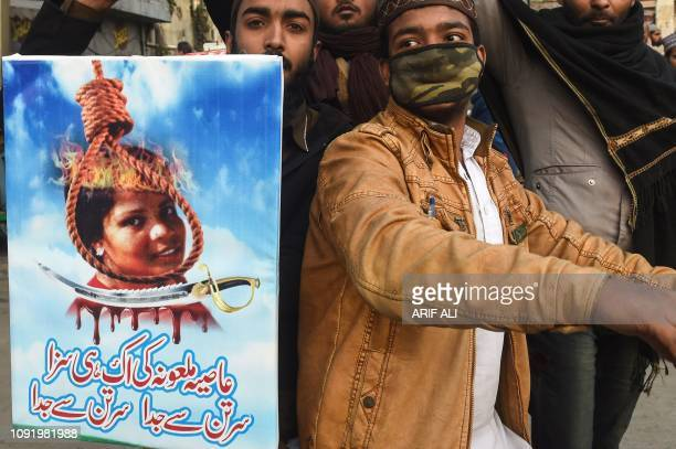 Pakistani Islamists hold a poster displaying the portrait of Asia Bibi a Christian Pakistani woman accused of blasphemy during a protest against the...