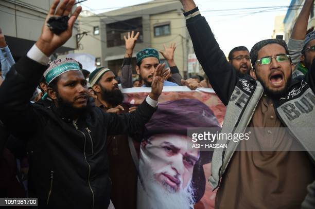 Pakistani Islamists shout slogans and hold a poster displaying the portrait of arrested hardline cleric Khadim Hussain Rizvi during a protest against...