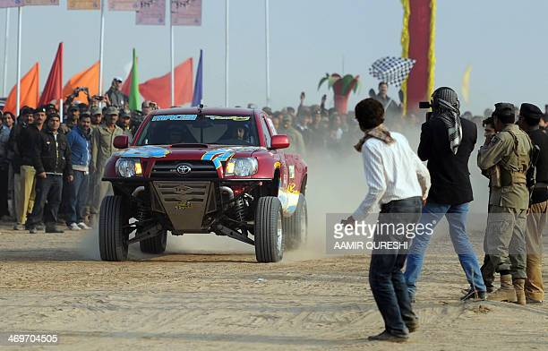 Pakistani jeep driver Nadir Magsi drives past spectators at the starting point of the Desert Jeep Rally in the Cholistan Desert in Derawar on...