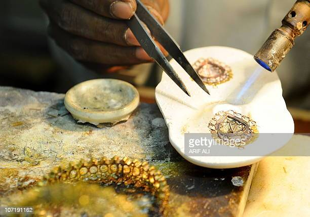 A Pakistani jeweller prepares a necklace at his gold workshop in Lahore on November 11 2010 Gold has surged to fresh pinnacles this week boosted by...