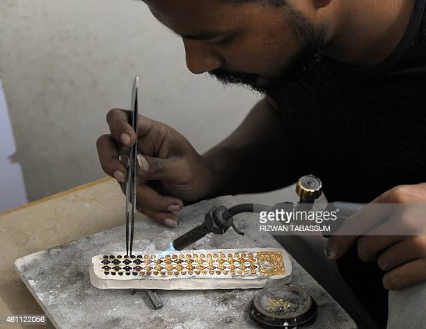 A Pakistani jeweller prepares pieces for a necklace at his gold workshop in Karachi on January 7 2015 The International Monetary Fund announced...