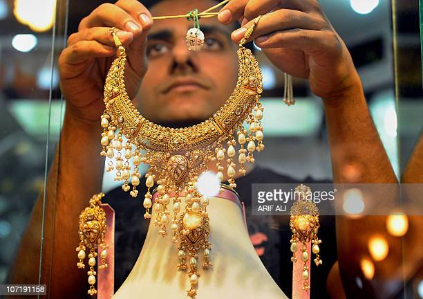 A Pakistani jeweller shows a necklace to a customer at his gold shop in Lahore on November 11 2010 Gold has surged to fresh pinnacles this week...