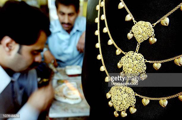 A Pakistani jewellery prepares a necklace at a gold shop in Peshawar 18 April 2006 The gold price has risen in Pakistan over the last several weeks...