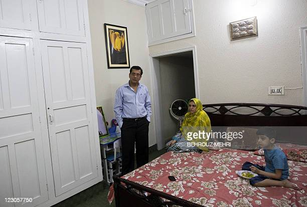 Pakistani journalist Arshad Raheem Loan, 39 years-old, poses with his wife, Fouzia Arshad and their son in their bedroom in Islamabad on July 31,...