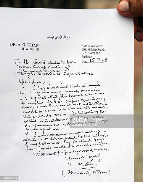 A Pakistani journalist shows a copy of a later written by detained Pakistani nuclear scientist Abdul Qadeer Khan outside a court in Islamabad on July...