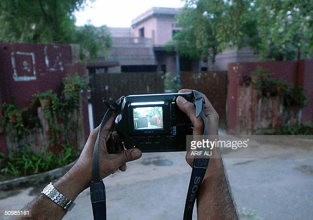 Pakistani journalist takes a photograph of the house of former Pakistani cricket hero Imran Khan in Lahore 22 June 2004 Khan and his British wife...