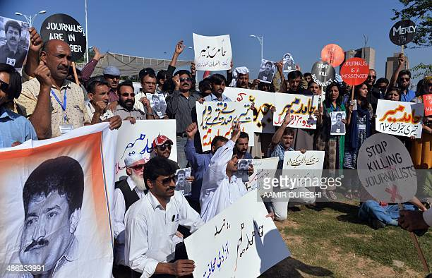 Pakistani journalists hold placards and photographs bearing the image of Geo television journalist Hamid Mir during a protest against the attack on...