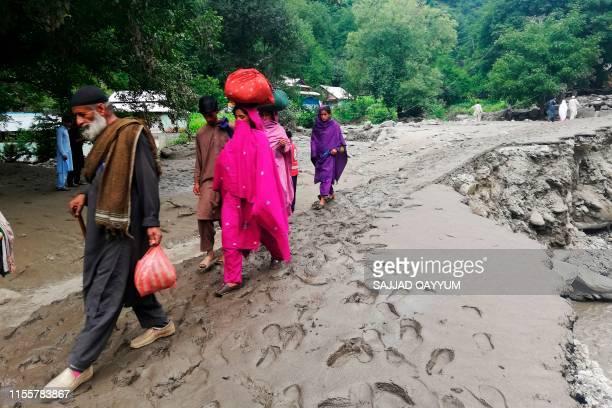 A Pakistani Kashmiri family walks along a damaged road following heavy monsoon rains in Neelum valley near the Line of Control in Pakistancontrolled...