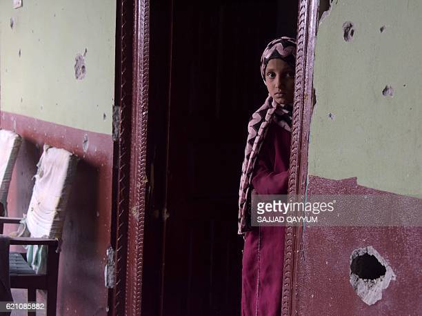 A Pakistani Kashmiri girl stands alongside a bulletriddled wall of her house following the crossborder shelling in the village of Peer Klanjer on the...