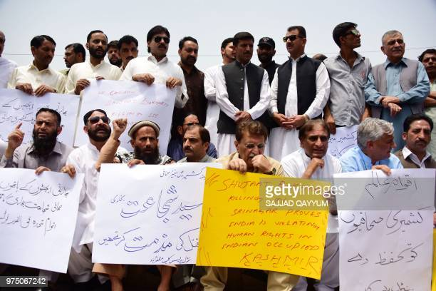 Pakistani Kashmiri journalists and residents hold placards during a protest against the killing of Indian Kashmiri editorinchief of the Srinagarbased...