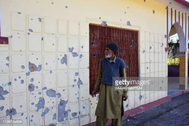 A Pakistani Kashmiri looks at a damaged bulletriddled wall of his house caused by crossborder firing at Dhanna village on the Line of Control that...