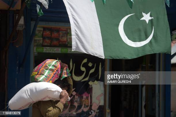 A Pakistani Kashmiri man carries food items at a market near the Line of Control the de facto border between Pakistan and India in Chakothi sector in...